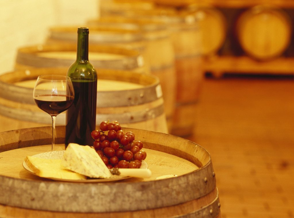 wine bottle with a wine glass and cheese on a barrel